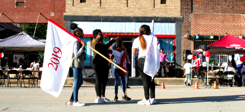 Flag-bearers Kai Mitchell (right), Paris Magsby (middle) and Shakira Zachary (left) gather on Main Street in Elaine with Arielle to learn their movement in the street. They look to the right to take in notes and landscape.